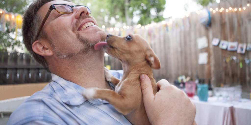 Man getting licked by a dog